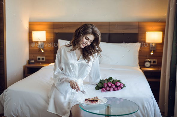 Smiling girl with breakfast in the hotel - Stock Photo - Images