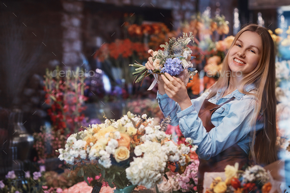 Smiling woman in uniform with flowers - Stock Photo - Images