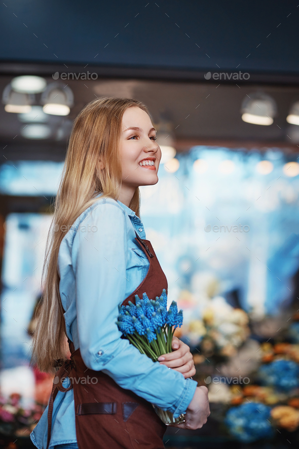 Smiling woman with muscari indoors - Stock Photo - Images