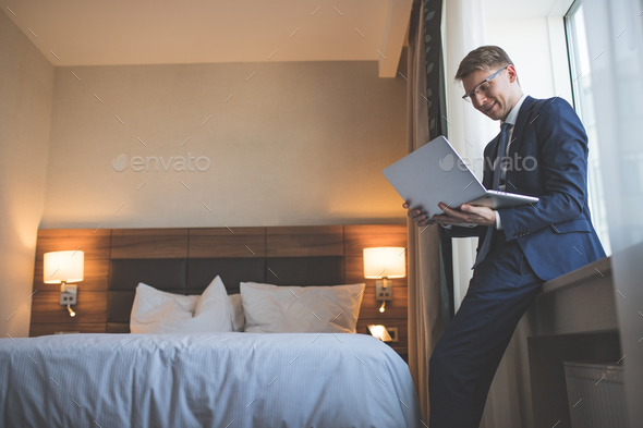 Smiling businessman with laptop in room - Stock Photo - Images