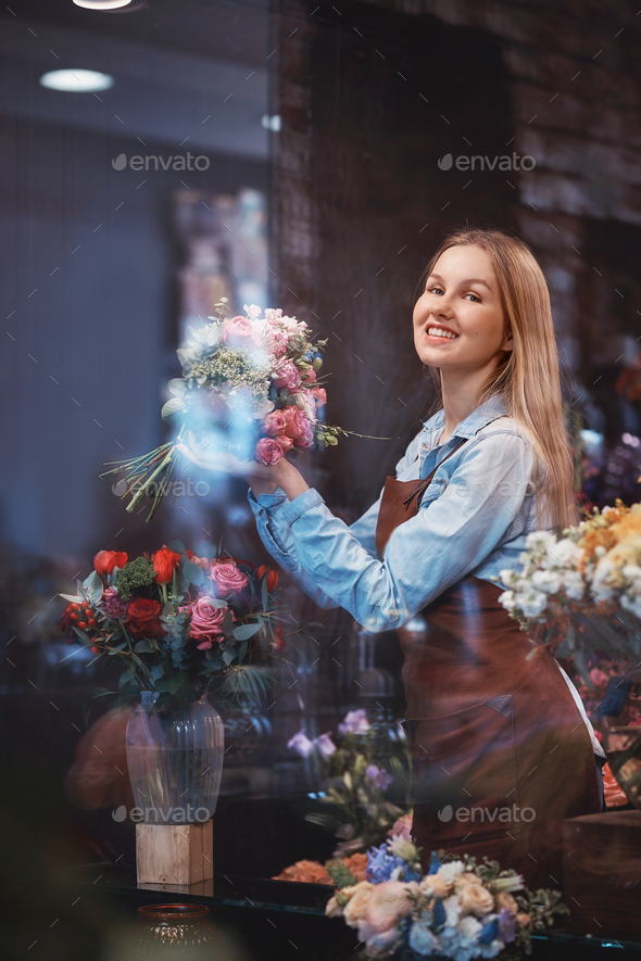 Smiling young florist in uniform - Stock Photo - Images