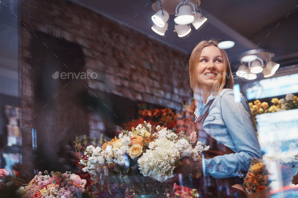 Smiling woman with flowers - Stock Photo - Images