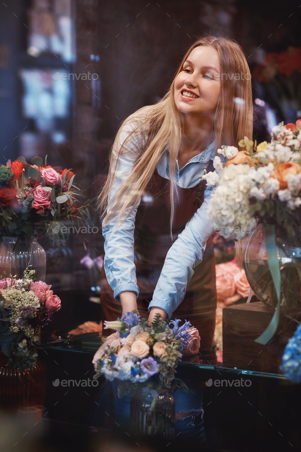 Smiling florist in uniform - Stock Photo - Images