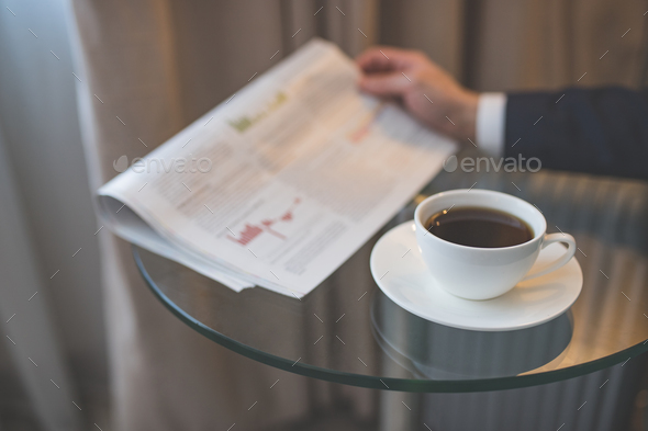 Man's hand with a newspaper and a cup of coffee - Stock Photo - Images