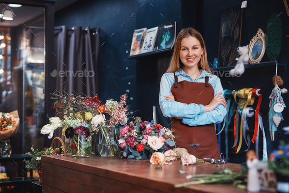 Smiling florist with flowers at the counter - Stock Photo - Images