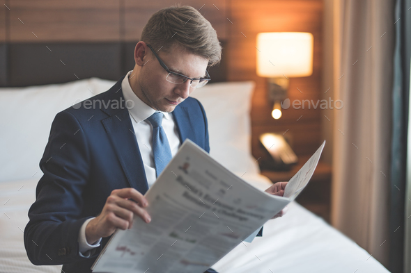 Young businessman reading a newspaper - Stock Photo - Images