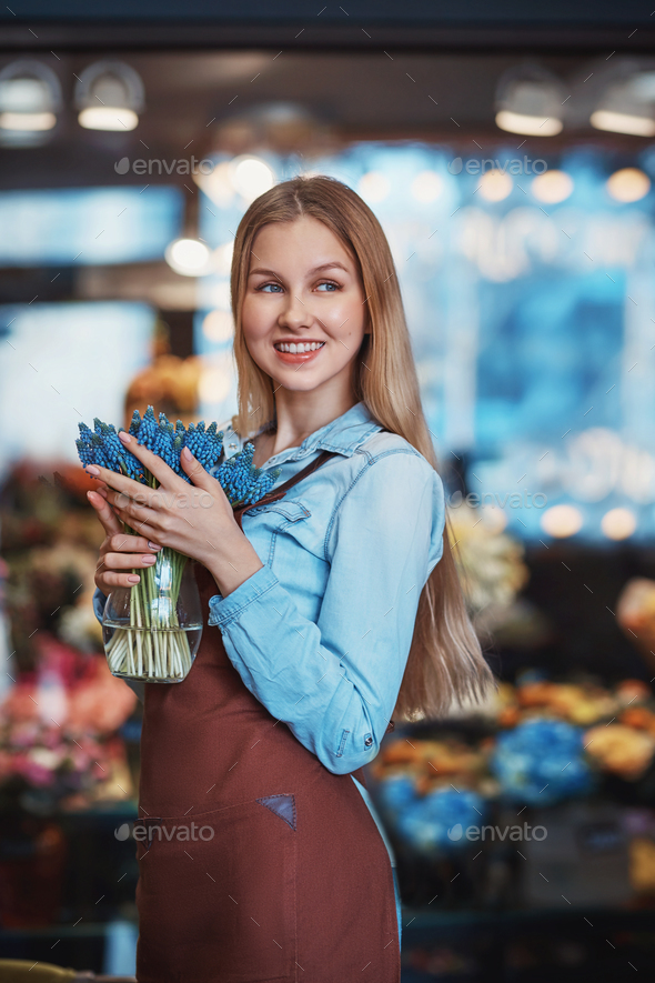 Smiling young woman with muscari - Stock Photo - Images