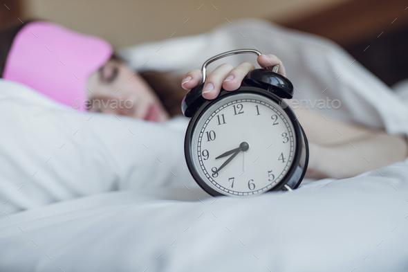 Sleeping girl with an alarm clock - Stock Photo - Images