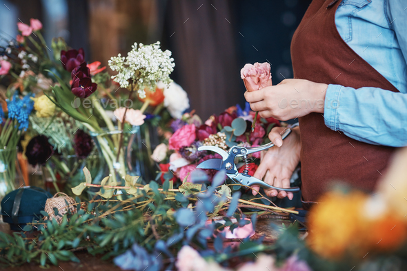 Young florist in uniform with flowers - Stock Photo - Images