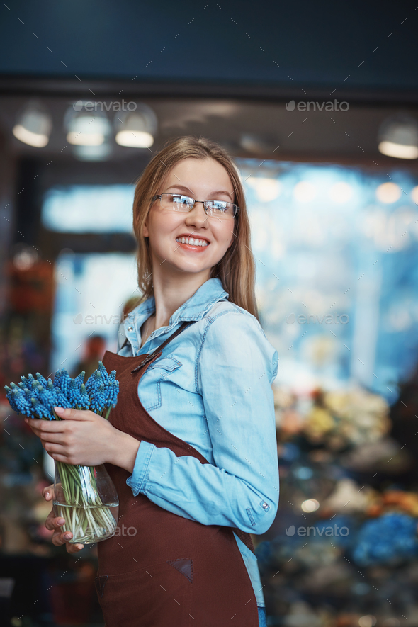 Smiling girl with flowers in a store - Stock Photo - Images