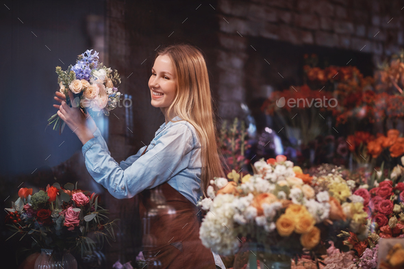 Smiling florist with flowers in a store - Stock Photo - Images