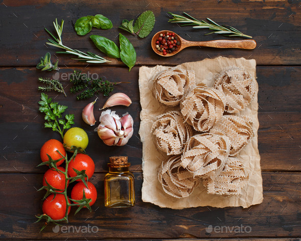 Whole wheat pasta tagliatelle, olive oil, vegetables and herbs - Stock Photo - Images