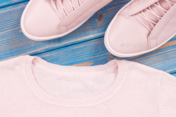 Pair of pink womanly leather shoes and sweater on old blue boards - Stock Photo - Images
