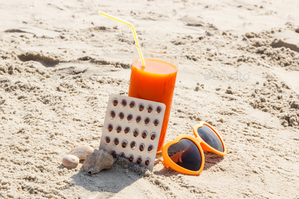 Medical pills, carrot juice and sunglasses on sand, vitamin A and beautiful, lasting tan - Stock Photo - Images