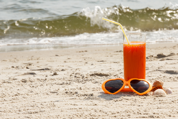 Carrot juice and sunglasses at beach, concept of vitamin A and beautiful, lasting tan - Stock Photo - Images