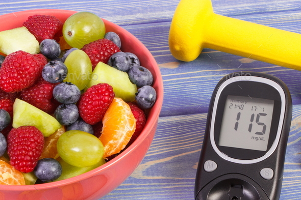 Fruit salad, glucometer for checking sugar level and dumbbells - Stock Photo - Images