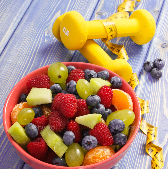 Fruit salad and centimeter with dumbbells, healthy lifestyle and nutrition concept - Stock Photo - Images