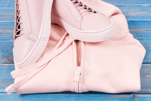 Womanly sweatshirt or hoodie and leather shoes on old boards - Stock Photo - Images