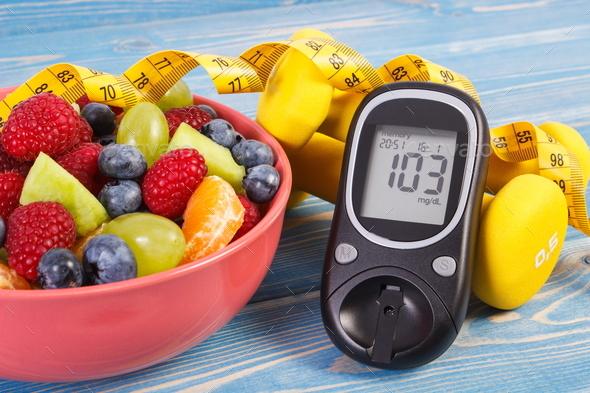 Fruit salad, glucose meter, centimeter and dumbbells - Stock Photo - Images