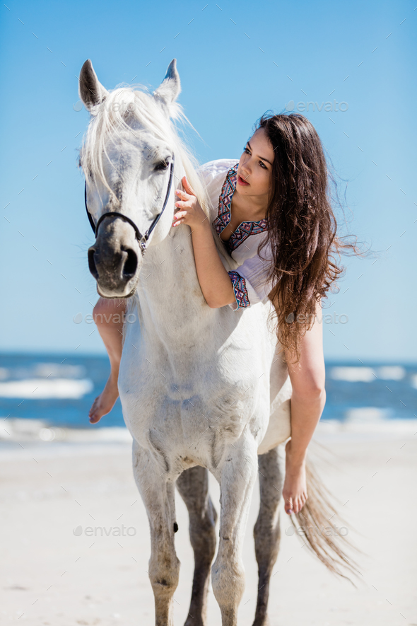 A portrait of a young girl sitting on a white horse - Stock Photo - Images