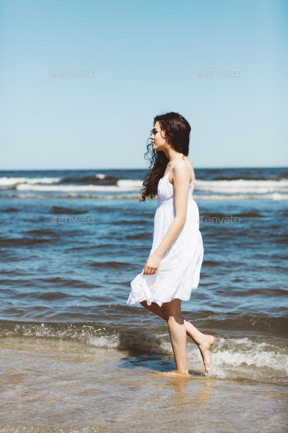 A girl in white dress walking alongside the ocean. - Stock Photo - Images