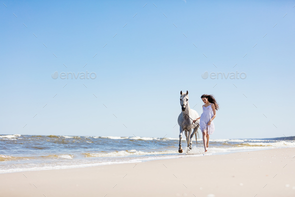 Young girl walking with white horse on the seashore. - Stock Photo - Images