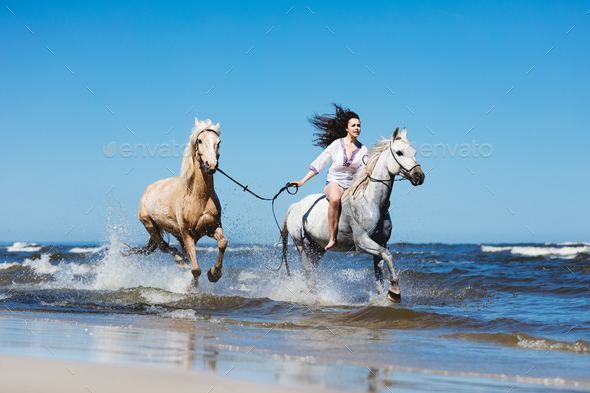 Girl galopading through the sea with two horses. - Stock Photo - Images