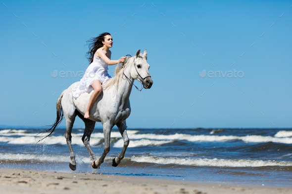 Girl storming through the beach on a white horse - Stock Photo - Images