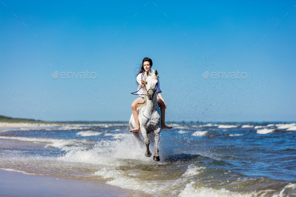 Girl galopading on a white horse in the sea - Stock Photo - Images