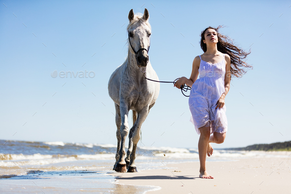 Young woman witth white horse running on the beach - Stock Photo - Images