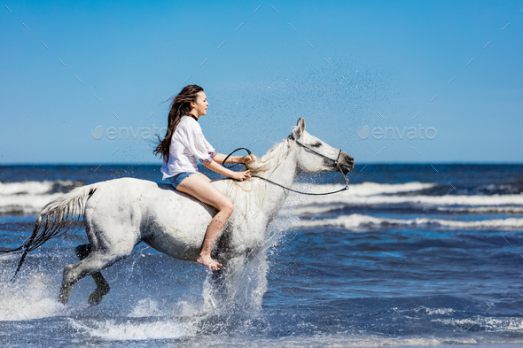 Young girl riding on the white horse through the ocean. - Stock Photo - Images