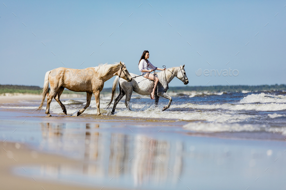 Young girl with two horses riding into the sea. - Stock Photo - Images