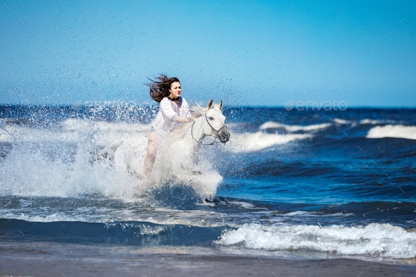 Girl on a white horse storming through the water - Stock Photo - Images