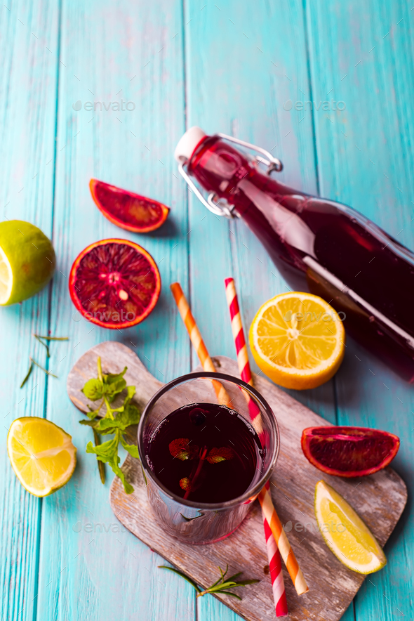Summer berry juice in a glass bottle with citrus on blue wooden background - Stock Photo - Images