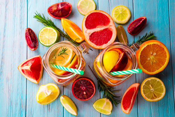 two glasses of citrus lemonade and a slice of fruit on a blue background - Stock Photo - Images