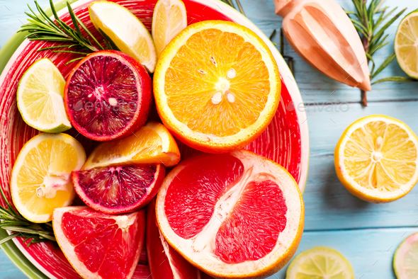 Sliced citrus fruit on the plate on blue wooden background - Stock Photo - Images