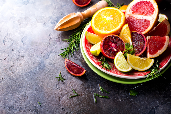 Sliced citrus fruit on the plate on stone dark background - Stock Photo - Images
