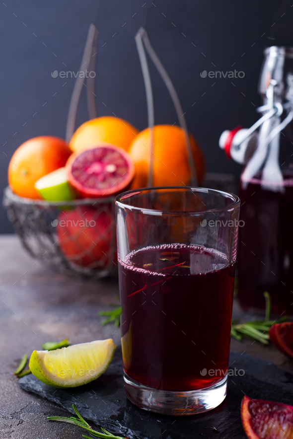 Summer berry juice in a glass with citrus on stone background - Stock Photo - Images