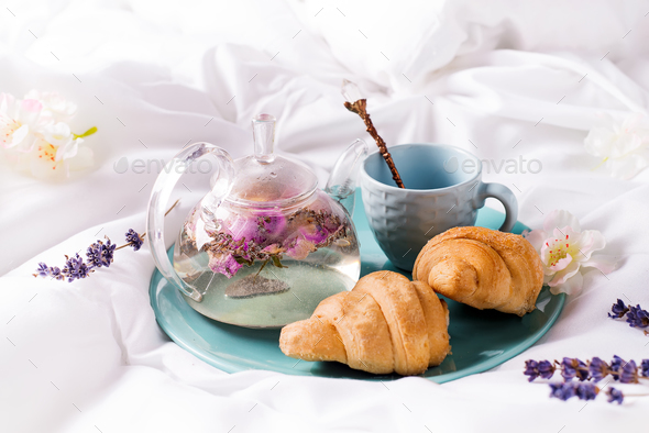 Breakfast in bed concept - french croissants with a cup of tea. - Stock Photo - Images