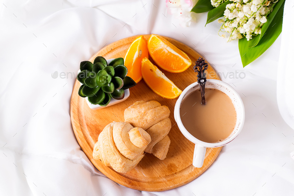 Breakfast in bed concept - french croissants with a cup of tea milk. - Stock Photo - Images