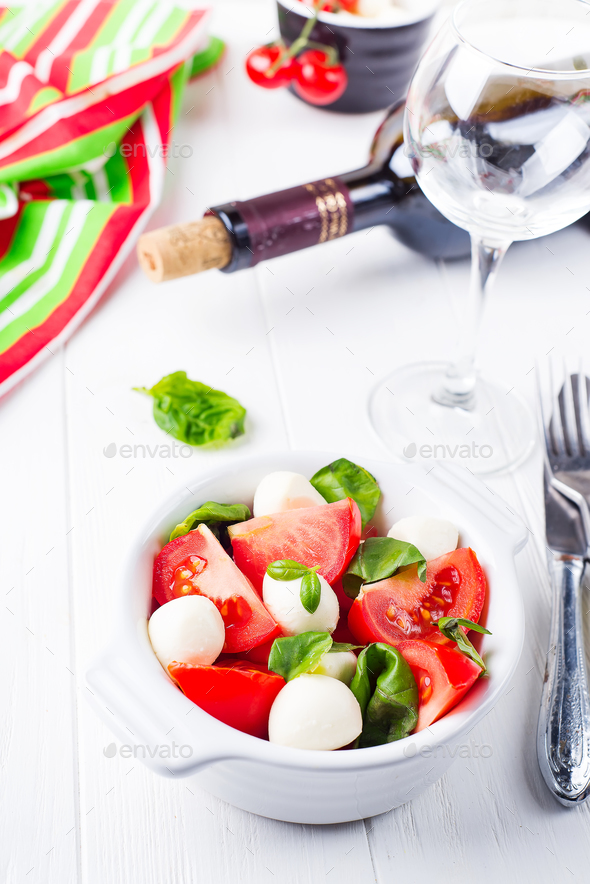 Caprese salad with mozzarella, tomato, basil and balsamic vinegar arranged on white bowl - Stock Photo - Images