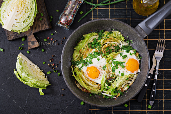Fried eggs with slices of young cabbage and greens. Nutritious breakfast. Top view. Flat lay - Stock Photo - Images