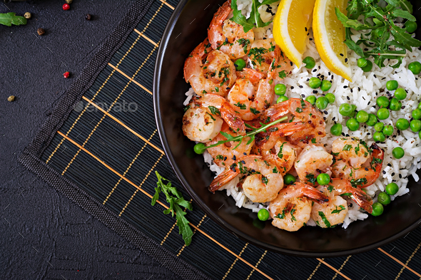 Rice with young green peas, shrimps and arugula in black bowl. - Stock Photo - Images