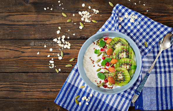 Oatmeal with kiwi, pomegranate, flax seeds and nuts. - Stock Photo - Images