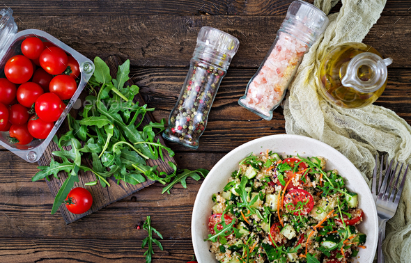 Salads with quinoa,  arugula, radish, tomatoes and cucumber in bowl  - Stock Photo - Images