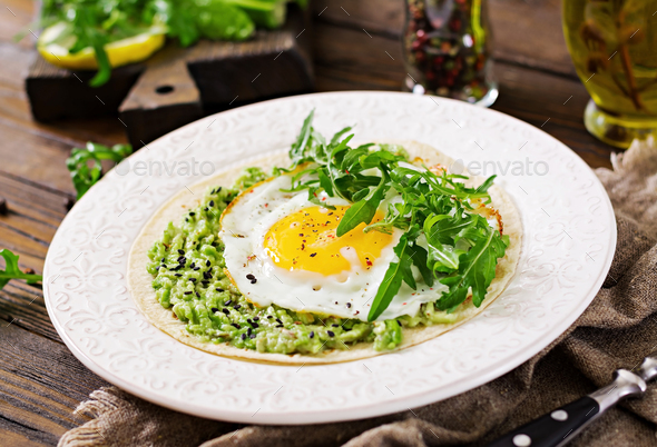 Tacos with guacamole, fried egg and arugula. Healthy food. Useful breakfast. - Stock Photo - Images