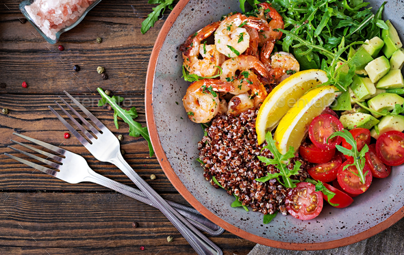 Delicious healthy Buddha bowl with shrimps, tomato, avocado, quinoa, lemon and arugula  - Stock Photo - Images