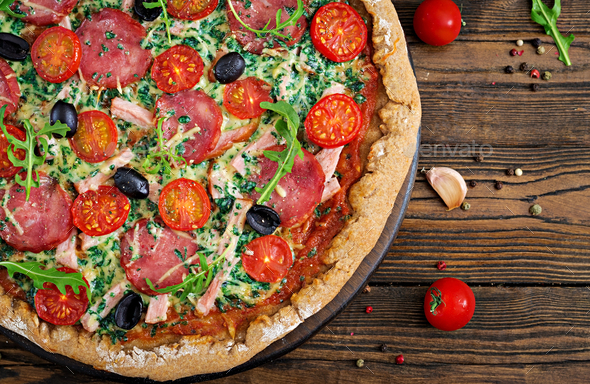 Pizza with salami, tomatoes, olives and cheese on a dough - Stock Photo - Images