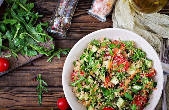 Salads with quinoa,  arugula, radish, tomatoes and cucumber in bowl on  wooden background. - Stock Photo - Images