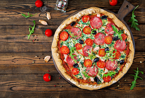 Pizza with salami, tomatoes, olives and cheese on a dough with whole wheat flour. Italian food.  - Stock Photo - Images